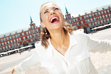smiling stylish traveller woman at Plaza Mayor rejoicing Editorial