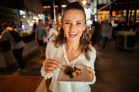 Portrait of happy young woman in white shirt at Mercado San Miguel trying local delicacies Фото со стока
