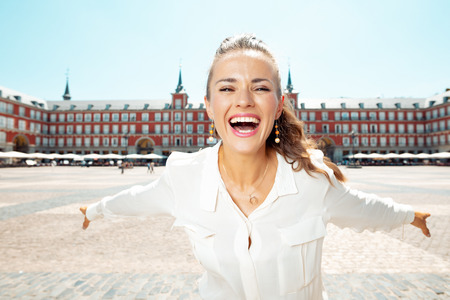 smiling young tourist woman at Plaza Mayor rejoicing Editorial