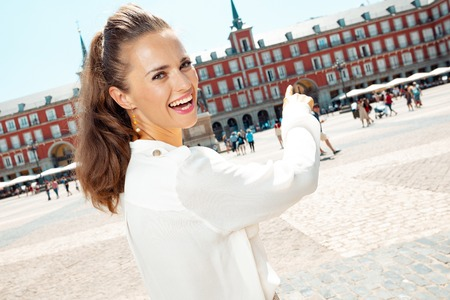 happy trendy woman at Plaza Mayor pointing at something