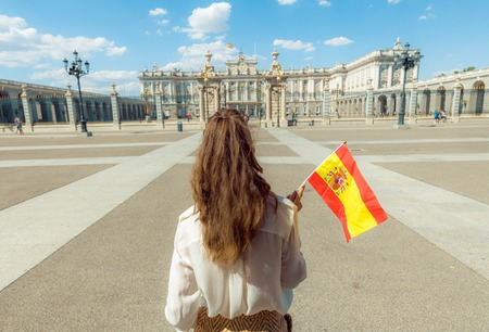 Seen from behind modern traveller woman with Spain flag against Royal Palace