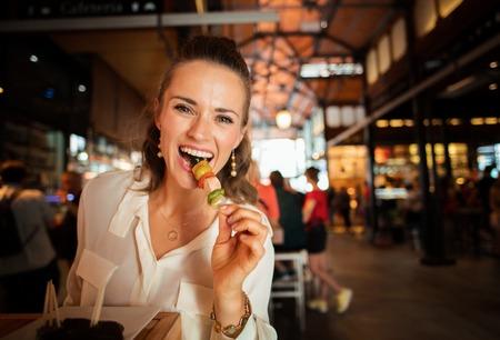 Smiling woman touriste à la mode en chemise blanche au marché de San Miguel en essayant des spécialités locales Banque d'images