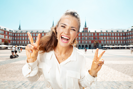 happy modern woman at Plaza Mayor showing victory gesture Editorial