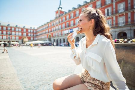 smiling stylish woman at Plaza Mayor eating Empanada Stock Photo - 108447411