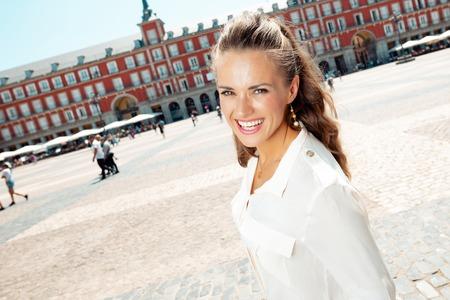 happy stylish tourist woman at Plaza Mayor Editorial