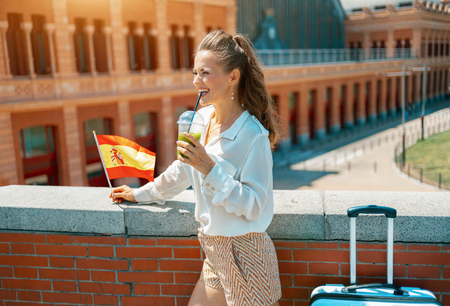 happy elegant tourist woman with trolley bag, Spain flag and green smoothie looking into the distance near Puerta De Atocha train station building