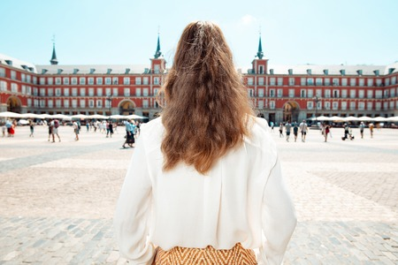 Seen from behind modern tourist woman at Plaza Mayor and exploring attractions