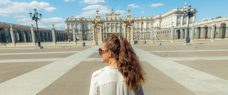 Seen from behind elegant woman in the front of Royal Palace looking into the distance Editöryel