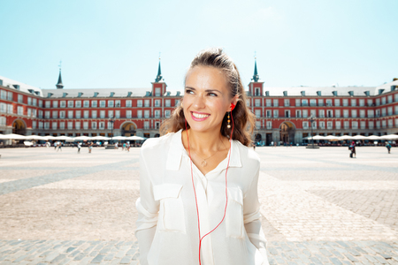 smiling young woman at Plaza Mayor looking into the distance and listening to an audio guide Editorial