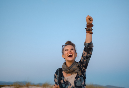 cheerful healthy traveller woman rejoicing against blue sky