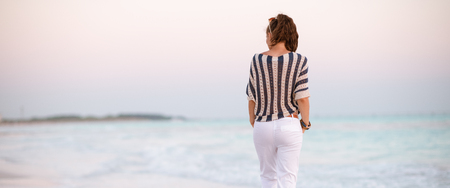 Seen from behind modern woman in white pants and striped shirt on the seashore at sunset walking