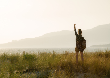 Seen from behind healthy woman in hiking gear rejoicing against mountain and ocean landscape at sunset