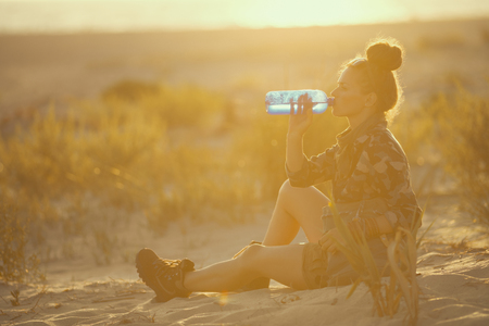 adventure traveller woman in hiking clothes on the seacoast at sunset drinking water from bottle