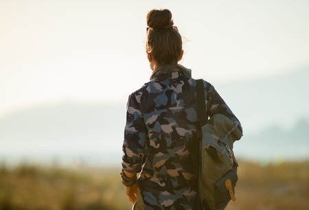 Seen from behind adventure tourist woman in hiking gear against mountain and ocean landscape at sunset Stock Photo