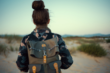 Seen from behind adventure traveller woman in hiking gear outdoors