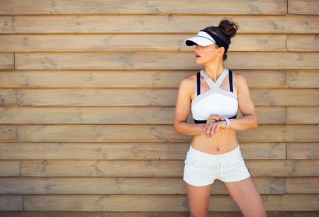 active woman jogger in sport clothes looking at copy space setting fitness bracelet against wooden wall