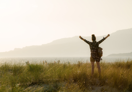 Seen from behind adventure woman in hiking gear rejoicing against mountain and ocean landscape at sunset