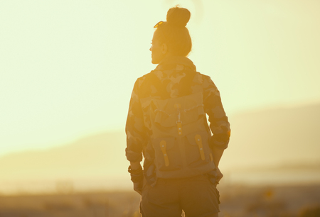 Seen from behind healthy tourist woman in hiking gear against mountain and ocean landscape at sunset
