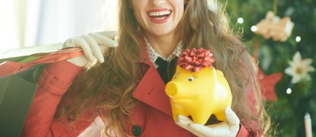 Closeup on happy young woman in red trench coat with shopping bags and yellow piggy bank near Christmas tree Stock Photo