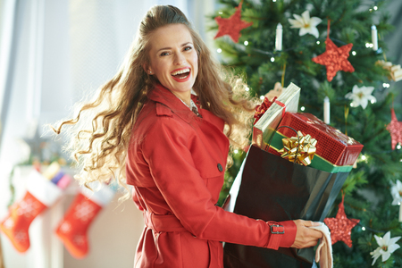 Portrait of cheerful young woman in red trench coat with shopping bag full of Christmas present boxes near Christmas tree Foto de archivo