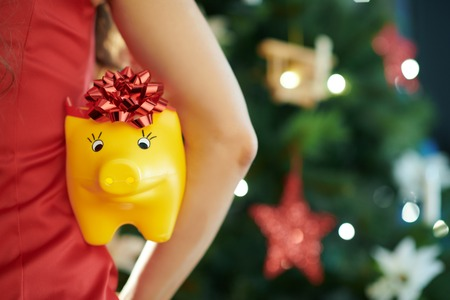 yellow piggy bank with red bow in hand of woman in red dress near Christmas tree holded by woman Stock Photo