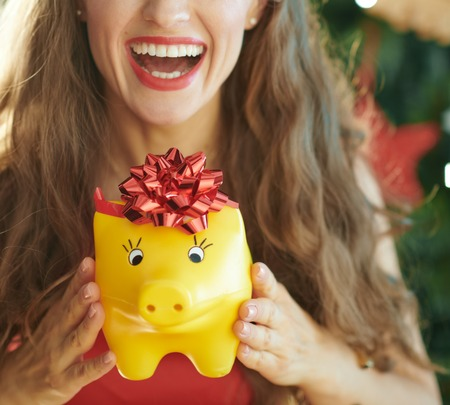 smiling modern woman showing yellow piggy bank with red bow near Christmas tree
