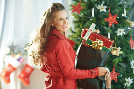 smiling young woman in red trench coat with shopping bag full of Christmas present boxes near Christmas tree