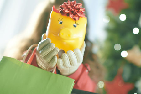 Closeup on yellow piggy bank in a hand of woman with shopping bags near Christmas tree Stock Photo