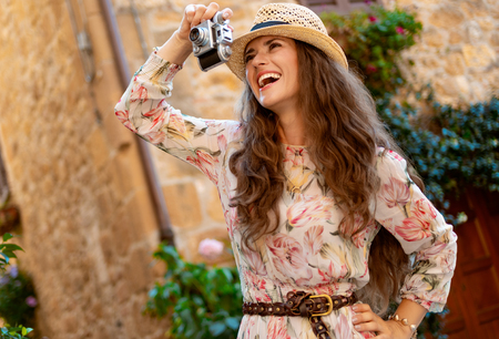 happy stylish traveller woman in long dress and straw hat taking photos with retro film photo camera in Pienza, Italy Stok Fotoğraf