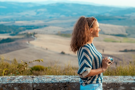Seen from behind stylish traveller woman in striped blouse with retro photo camera in the front of scenery of Tuscany