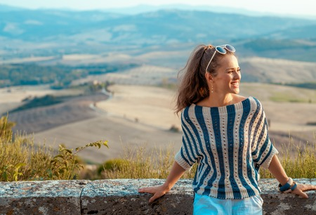 smiling elegant traveller woman in striped blouse in Tuscany looking into the distance
