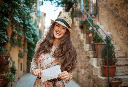 Portrait of happy stylish tourist woman in long dress and straw hat with map in old Italian town