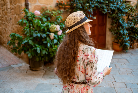 Seen from behind stylish traveller woman in long dress and straw hat with map in old Europe town