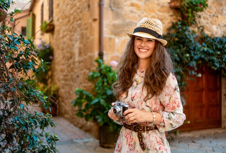 Portrait of smiling elegant traveller woman in long dress and straw hat with retro film photo camera in old Europe town