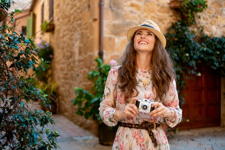 smiling modern traveller woman in long dress and straw hat with retro film photo camera sightseeing in old Europe town