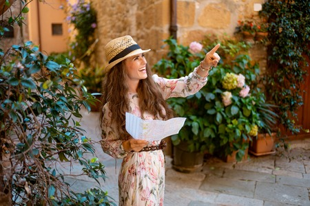 happy modern traveller woman in long dress and straw hat with map pointing at something in old Europe town