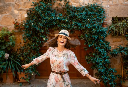 happy stylish traveller woman in long dress and straw hat in old Europe town having fun time