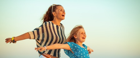 happy stylish mother and daughter on the beach at sunset rejoicing Stock Photo