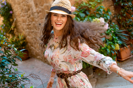 smiling young tourist woman in long dress and straw hat in old Italian town rejoicing 版權商用圖片
