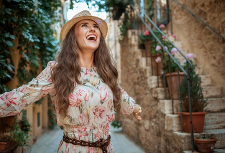 happy elegant traveller woman in long dress and straw hat in old Italian town rejoicing