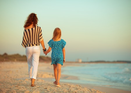 Seen from behind stylish mother and daughter on the seacoast in the evening walking