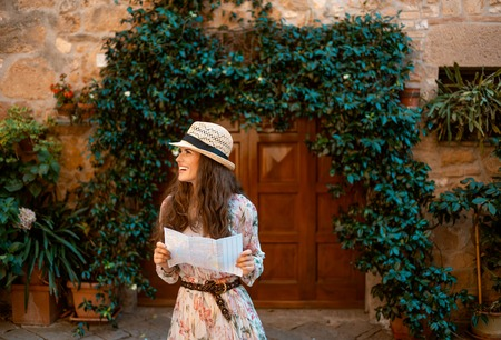 smiling stylish tourist woman in long dress and straw hat with map looking aside in old Europe town 版權商用圖片