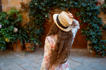 Seen from behind elegant traveller woman in long dress and straw hat in old Italian town having excursion Stock Photo