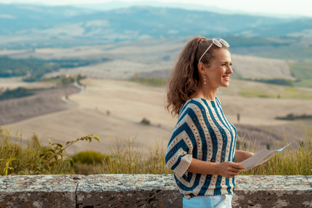 smiling elegant tourist woman in striped blouse with map looking into the distance against scenery of Tuscany 版權商用圖片