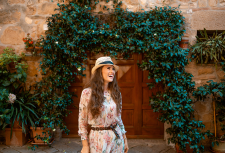 smiling elegant traveller woman in long dress and straw hat in Pienza, Italy having walking tour