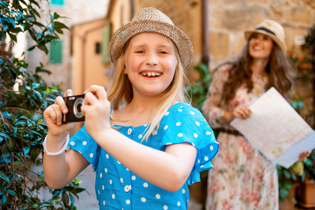 happy child taking photo with digital camera and mother with map in background in old Italian town