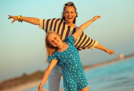 smiling modern mother and child on the seacoast in the evening having fun time Stock Photo