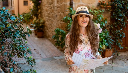 smiling stylish traveller woman in long dress and straw hat with map looking into the distance in Pienza, Italy