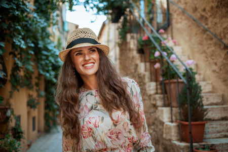 happy young traveller woman in long dress and straw hat in old Europe town having walking tour