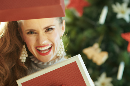 smiling trendy housewife playing with Christmas present boxes near Christmas tree